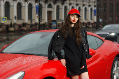 Sexy woman against red sport car Royalty Free Stock Photo