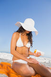 Sexy woman applying sun cream while sitting on her towel Stock Images