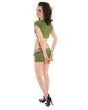 Woman in army clothes. Young woman in green army top and shorts looking back over shoulder, white background royalty free stock photography