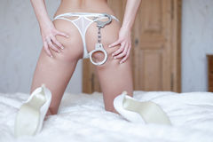 Sexy woman ass with handcuffs on bed Stock Images