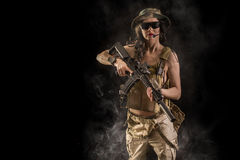 Sexy woman with assault rifle. Sexy woman soldier with an assault rifle on a black background Stock Photography