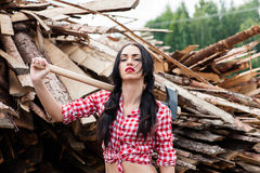 Sexy woman ax in hand in a plaid shirt Stock Photography