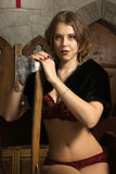 Sexy woman with axe in a medieval castle Stock Photography