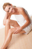 Sexy woman in a bath towel. Sexy young blonde woman with bare legs sitting on the floor in a bath towel in a personal hygiene concept Stock Photography