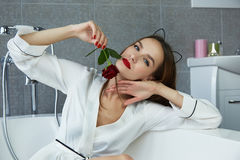Woman in bathroom in silk robe rose Valentine's day. Beautiful young woman with dark hair, evening make-up, red lips and manicure sitting in the bathroom in a stock images