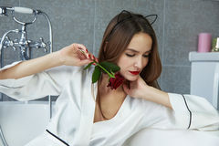 Woman in bathroom in silk robe rose Valentine's day. Beautiful young woman with dark hair, evening make-up, red lips and manicure sitting in the bathroom in a royalty free stock photo
