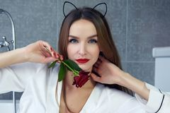 Woman in bathroom in silk robe rose Valentine`s day. Beautiful young woman with dark hair, evening make-up, red lips and manicure sitting in the bathroom in a stock photos