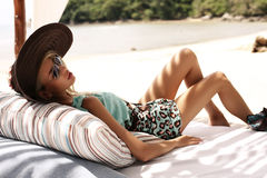 Sexy woman in beach clothes ,hat and sunglasses relaxing on beach Royalty Free Stock Photos