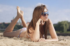 Sexy woman on beach in sunglasses. Woman laying on the sandy, city beach Royalty Free Stock Photography