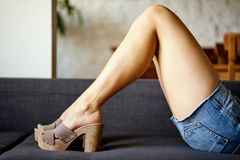 Woman with beautiful slim legs lies on couch in denim shorts and wooden wedge heels. Woman with beautiful slim legs lies on gray couch in denim shorts and stock images