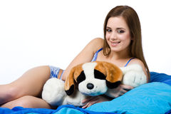 Sexy woman in the bed with her plush dog Royalty Free Stock Photography
