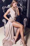 Sexy woman in beige silk dress sitting on the black armchair Stock Images