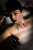 woman in a beige swimsuit and black hat in a shadow stripe Stock Photography