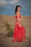 Sexy woman belly dancer arabian in desert dunes. At the afternoon Stock Images
