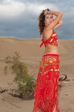 Sexy woman belly dancer arabian in desert dunes. At the afternoon Stock Photography