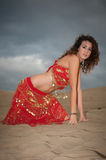 Sexy woman belly dancer arabian in desert dunes. At the afternoon Stock Image