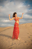 Sexy woman belly dancer arabian in desert dunes. At the afternoon Royalty Free Stock Image