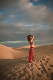 Sexy woman belly dancer arabian in desert dunes. At the afternoon Royalty Free Stock Images