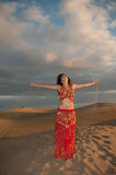 Sexy woman belly dancer arabian in desert dunes. At the afternoon Stock Photos