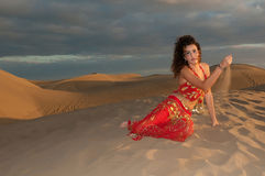 Sexy woman belly dancer arabian in desert dunes. At the afternoon Royalty Free Stock Photography