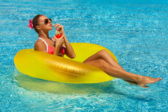 Sexy woman in bikini enjoying summer sun and tanning during holidays in pool with a cocktail. Sexy woman in bikini enjoying summer sun and tanning during Stock Photo