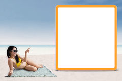 Sexy woman in bikini pointing at copyspace Stock Images