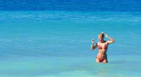 Woman in bikini posing in a sea. Woman in red bikini posing in a blue sea royalty free stock photo
