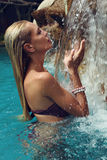 woman in bikini relaxing under waterfall in Thailand Royalty Free Stock Images