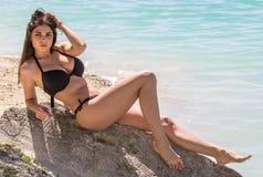 Sexy woman in bikini on sea background. Young sexy woman in a black bikini on sea background Royalty Free Stock Photos