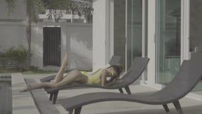 Sexy woman in bikini at the swimming pool in evening time stock footage