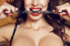 Sexy woman bite handcuffs Royalty Free Stock Image