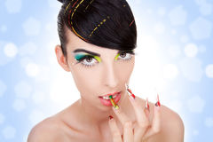 Sexy woman biting her fancy nails. Cosmetics and nail products. Sexy beautiful female model with fashion make-up, sexy  lips,  makeup, bright nails with fancy Royalty Free Stock Image