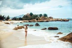 Sexy woman in black bikini swimwear walking at the ocean beach. Young beautiful girl with an excellent figure posing Stock Photos