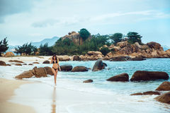 Sexy woman in black bikini swimwear walking at the ocean beach. Young beautiful girl with an excellent figure posing Royalty Free Stock Photography