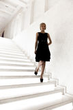 Sexy woman in black dress descending from marble stairway Stock Images