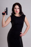 Sexy woman in black dress holding gun over grey Stock Image