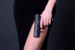 woman in black dress holding gun over grey Stock Image