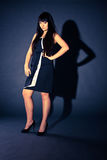 Sexy woman in black dress posing against dark background Royalty Free Stock Photos