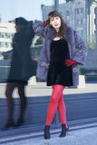woman in a black dress, red tights and a fur coat Stock Images