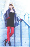 woman in a black dress, red tights and a fur coat Royalty Free Stock Photos
