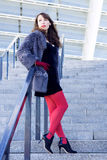 Sexy woman in a black dress, red tights and a fur coat Stock Image