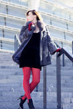 Sexy woman in a black dress, red tights and a fur coat Royalty Free Stock Image