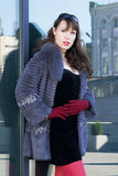 woman in a black dress, red tights and a fur coat Royalty Free Stock Images