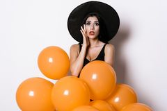 A sexy woman in a black dress and a witch hat posing with orange balloons and portraying anxiety Stock Image