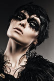 woman with black feather on eyes Stock Image