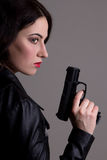 Sexy woman in black with gun over grey Royalty Free Stock Photography