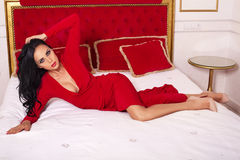 Sexy woman with black hair in elegant dress lying on bed Royalty Free Stock Image