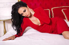 Sexy woman with black hair in elegant red dress lying on bed Stock Photo