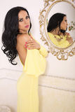 Sexy woman with black hair in elegant yellow dress with bijou Royalty Free Stock Image