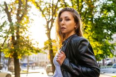 Sexy woman in black leather jacket on the street with backlight sun. Street fashion photography